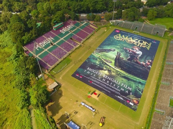 'Amazon Obhijaan' poster launched today. The film releasing on 22nd December. Scalling at a whopping 60,800 sq.ft ( 5640 sq.meters) The Amazon Obhijaan poster unveiled at Mohun Bagan ground on Saturday. This gigantic poster comfortably breaks the film poster record set by Baahubali which was 51,600 sq ft ( 4794 sq.meters). A large crowd flocked to the football ground to see the massive poster of the film. Amazon Obhijaan film poster is 97 meter long (320 feet) and 58 meter wide (190 feet) if placed vertically would be taller than Big ben (96 meters) or Qutub Minar ( 73 meters).