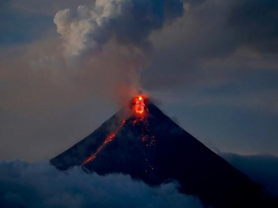 Lava is spilling from a Philippine volcano that has been sending up columns of ash over farmland and towns, coating them in grey during a nearly two-week eruption. Photo: AP