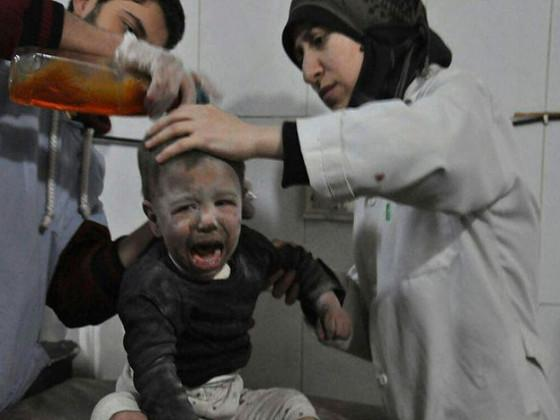 Syrian paramedics treat a kids who was wounded during airstrikes and shelling by Syrian government forces, at a makeshift hospital, in Ghouta, suburb of Damascus, Syria. (Image: Ghouta Media Center via AP)